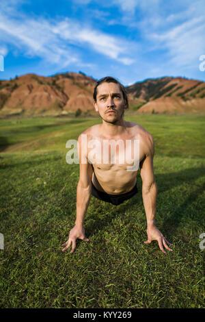 shirtless man practicing yoga on rockcolchuck lake