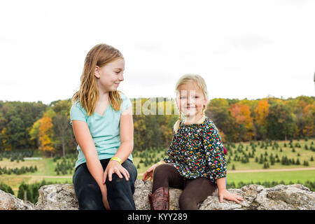 Portrait of smiling girl sitting by sister on rock against clear sky - Stock Photo