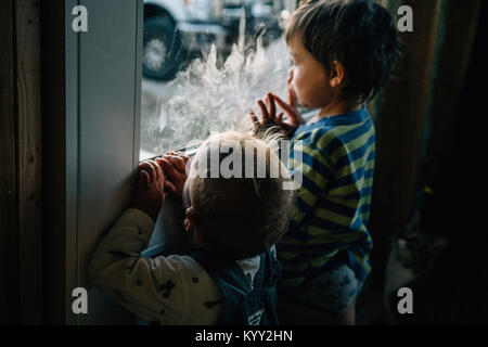 Rear view of siblings looking through window at home - Stock Photo