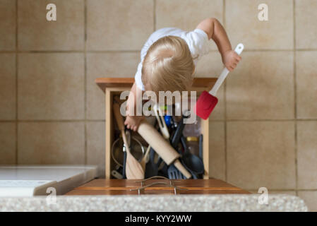 Overhead view of baby boy removing kitchen utensils from drawer - Stock Photo