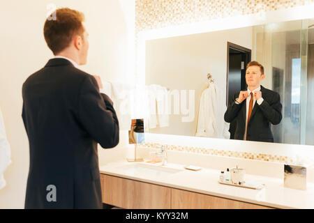 Businessman adjusting necktie in hotel bathroom - Stock Photo