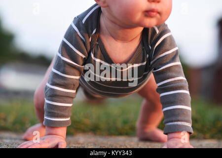 Low section of baby boy trying to stand at backyard - Stock Photo