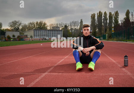 Full length of male athlete listening music while sitting on running track - Stock Photo