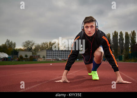 Full length of male athlete listening music while taking position at running track - Stock Photo