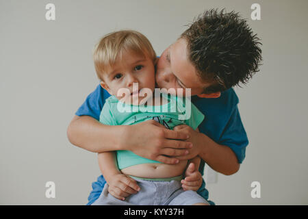 Portrait of cute baby boy with brother kissing him against wall at home - Stock Photo