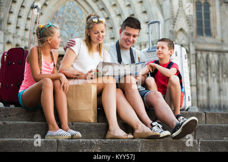 Young positive family of tourists resting on stairs reading paper map - Stock Photo