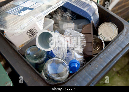 Wheelie bin full of domestic recycling waste, glass bottles, tin cans and plastic bottles, plastic waste, Recycling. - Stock Photo