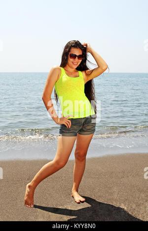 Long hair Asian beauty posing on a windy tropical beach - Stock Photo