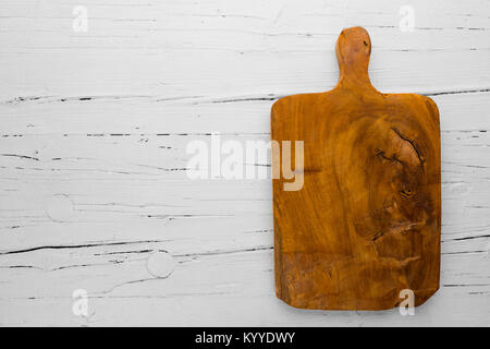 Vintage cutting board with copy space on white wooden background, view from above - Stock Photo