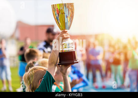 Young Athlete Holding Trophy. Youth Sport Soccer Team with Trophy. Boys Celebrating Sports Achievement. Winning - Stock Photo