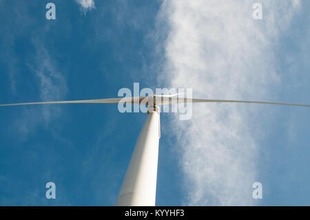 Blades of a wind turbine rotate as clouds pass overhead - Stock Photo