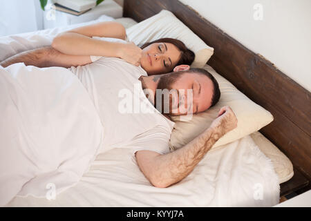 a man with a woman sleeping in beds bedroom - Stock Photo