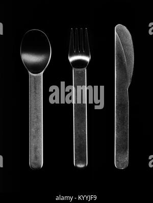 Cheap plastic cutlery set isolated on black. Disposable clear silverware -  knife, spoon and fork arranged in a - Stock Photo