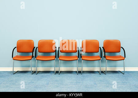 Five waiting room chairs in a row against a wall in an empty room - Stock Photo