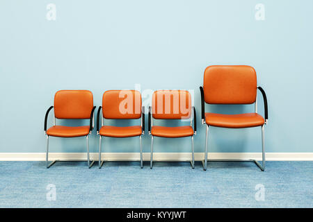 One large and three small chairs in a row against a wall in an empty room - concept image - Stock Photo