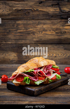 Tasty breakfast. Appetizing croissant with salami and, cheese and tomatoes - Stock Photo
