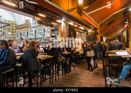 Bologna, Italy - People sitting out eating in restaurants, cafes and bars in Via Pescherie Vecchie, a street in - Stock Photo