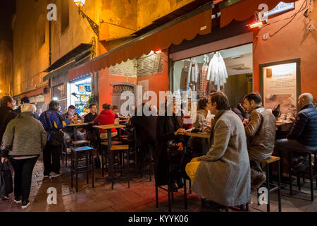 People sitting out eating in restaurants, cafes and bars in Via Pescherie Vecchie, a street in Bologna city, Italy - Stock Photo