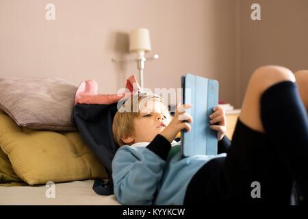 Boy using digital tablet in the bedroom in the bedroom - Stock Photo