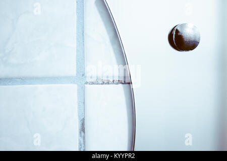 tiled wall and the edge of the mirror in the bathroom - Stock Photo