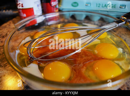 Making french toast. Eggs in clear glass mixing bowl with metal whisk, egg beater. Egg carton in backgound  with - Stock Photo