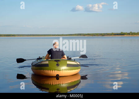 Man in an inflatable boat floats on the river, the view from the back - Stock Photo