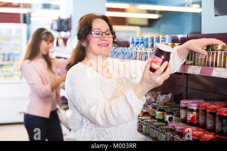 Two joyful smiling women choosing confiture in food store - Stock Photo
