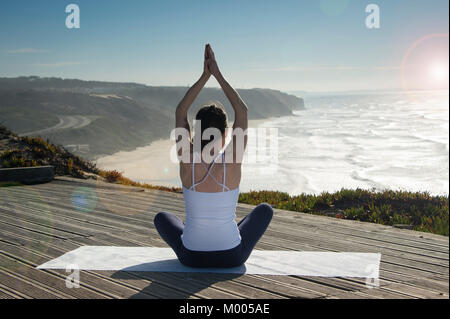 woman sitting in the lotus position meditating with a view over the sea and cliffs. Back view. - Stock Photo
