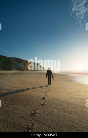 woman walking along a deserted beach carrying a camera. Footsteps in the sand. Lens Flare. - Stock Photo