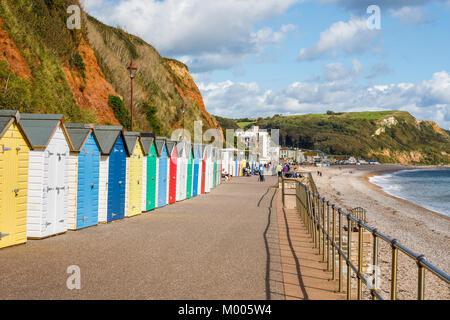 Colourful beach huts under the cliffs along the seafront promenade at Seaton, Devon, in the Jurassic Coast World - Stock Photo