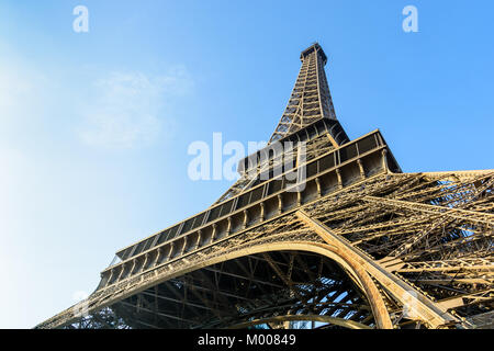 Dynamic view from below of the Eiffel Tower against blue sky. - Stock Photo