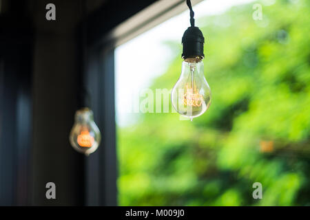 Incandescent light bulbs hanging on the interior ceiling, selective soft focus with blurred background. - Stock Photo