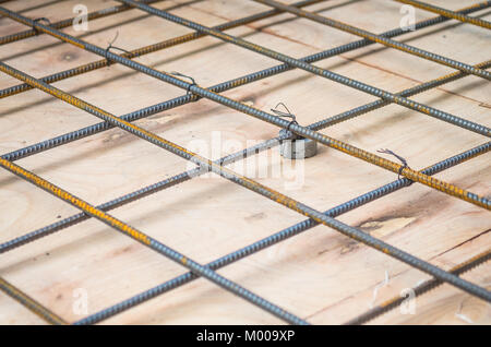 Rebars steel wire mesh, which is supported by mortar cover box and wooden plate for precast concrete flooring on - Stock Photo