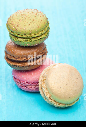 French luxury colorful macarons dessert cakes on blue wood background with sugar on top - Stock Photo