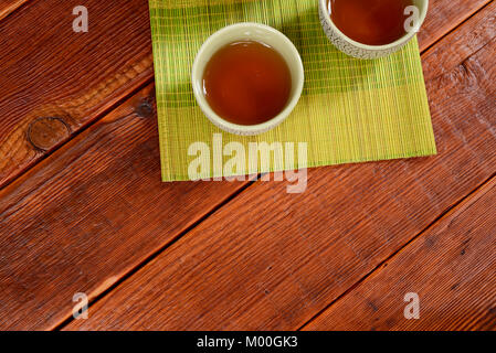 Still life of traditional Chinese crackle glaze tea cups filled with oolong tea on a green bamboo mat on top of - Stock Photo