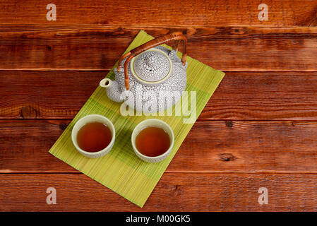 Still life of a traditional Chinese tea pot and matching cups filled with oolong tea on a green bamboo mat on top - Stock Photo