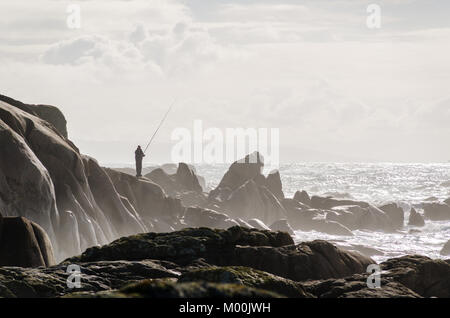 Fisherman fishing on coastline rocks. Brown tones - Stock Photo