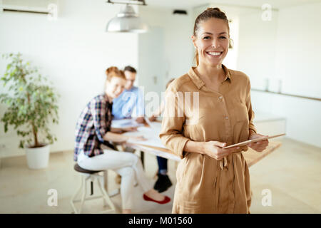 Image of business woman looking at tablet - Stock Photo