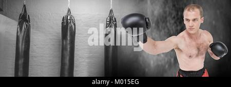 Boxer man with punching bags in gym - Stock Photo