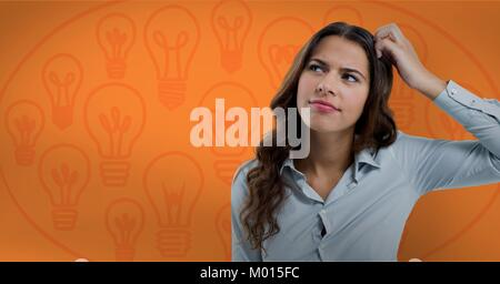 Confused woman scratching her head looking up in front of a orange background with bulbs - Stock Photo
