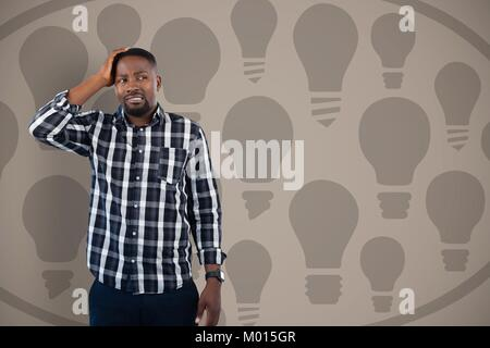 Confused man holding his head looking on the right on bulbs pattern - Stock Photo