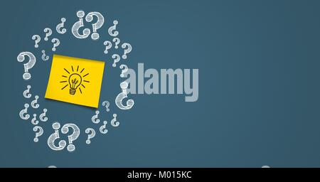 Idea on a post it surrounded by question marks on grey background - Stock Photo