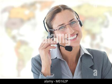Travel agent woman wearing headset in front of world map - Stock Photo