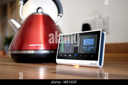 British Gas Smart meter showing how much energy being used in household with boiling kettle in background - Stock Photo