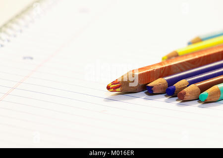 Seven wooden color pencils next to each other on a paper sheet of a notebook with spiral. - Stock Photo