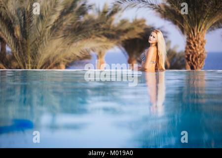 Luxury Resort. Woman Relaxing In Infinity Swimming Pool Water. Beautiful Happy Healthy Female Model Enjoying Summer - Stock Photo