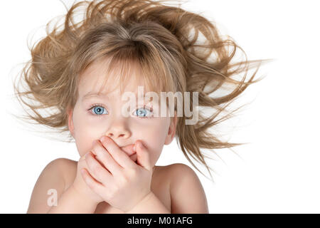 Little beautiful girl with blue eyes and tousled hair covered her mouth with her hands, isolated on white background - Stock Photo