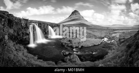 Black and white panorama of the Kirkjufell waterfall with the famous mountain in the background. - Stock Photo