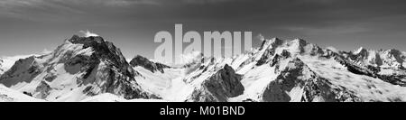 Black and white panoramic view of snow-capped mountain peaks with mount Dombay-Ulgen and sky with clouds at sun - Stock Photo