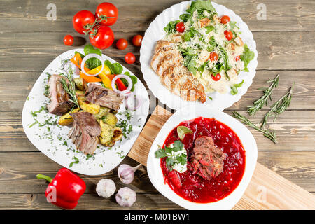 Different dishes on wooden table, top view. Vegetable beet soup, rack of lamb with fried potato, Grilled chicken - Stock Photo